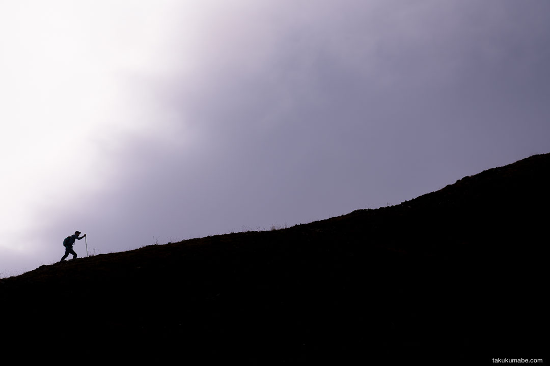 A silhouette of a hiker on a ridgeline